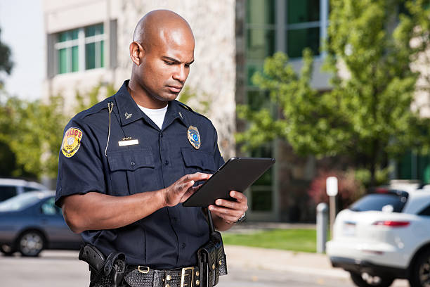 policjant za pomocą komputera, tabletu - policja zdjęcia i obrazy z banku zdjęć