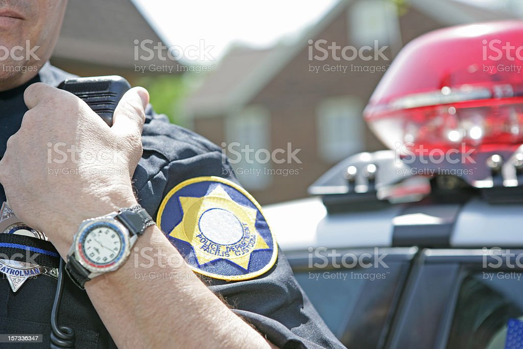 Police officer using radio to call for backup stock photo