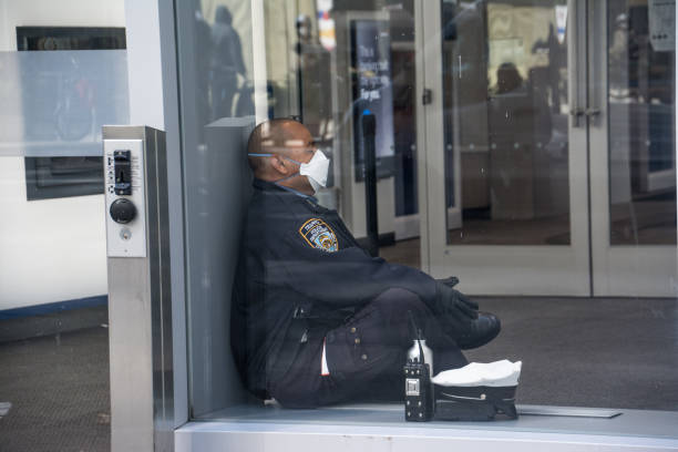 Police Officer with Face Mask Sitting Stressed - Covid-19 New York City, United States - April 23rd, 2020: A police officer sits crosslegged, taking a break with a face mask on flatten the curve stock pictures, royalty-free photos & images