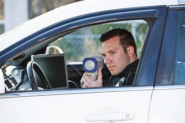 polizist mit radar pistole - geschwindigkeitskontrolle stock-fotos und bilder