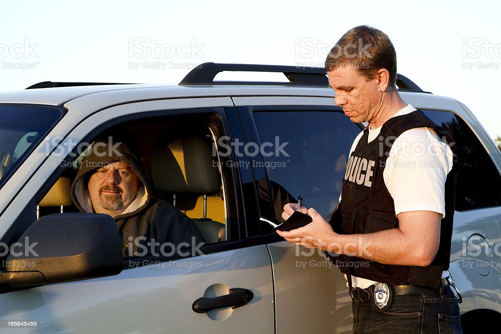 Police officer writing man ticket stock photo