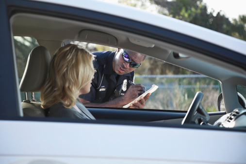 African American police officer (20s) giving woman a traffic ticket.