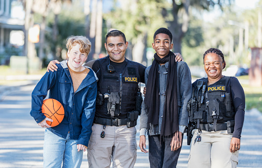 Community policing - two police officers standing with two youths in a public park. One officer, a young Hispanic man, is standing between the two boys, an African-American 14 year old teenager, and a 12 year old boy holding a basketball. The other police officer is an African-American woman. They are smiling at the camera.