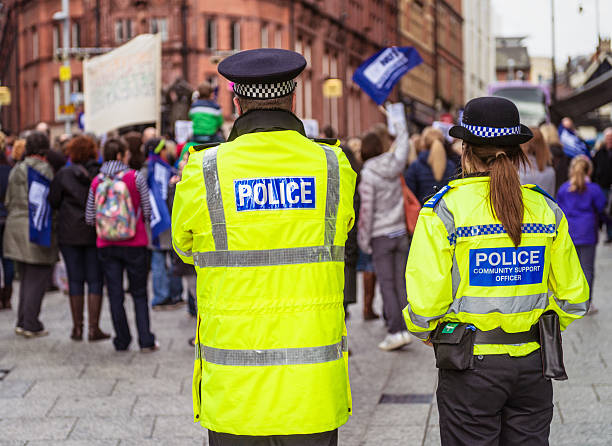Police Officers at a peaceful demonstration Nottingham, UK - March 26, 2014: Two police officers watching a peaceful demonstration by trade union members on the day of a national strike by teachers, in protest of Department of Education policies. police meeting stock pictures, royalty-free photos & images