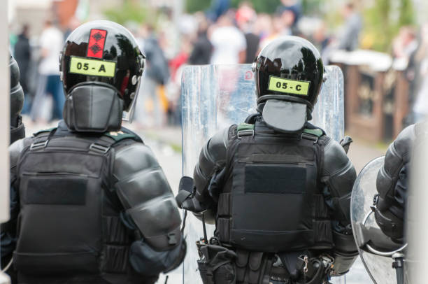 Police officers from the PSNI dressed in riot armoured clothing with protective shields and helmets. Belfast, Northern Ireland. 09 Aug 2015 - PSNI riot squad dressed in protective clothing with shields , helmets and body protection, move in to kettle loyalist rioters on the streets of Belfast, Northern Ireland.  Rioting between loyalists and republicans is common, even 30 years after the end of