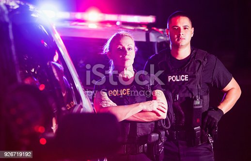 Two multi-ethnic police officers at night wearing bulletproof vests, standing beside police cars with emergency lights flashing. The policewoman is in her 40s and her Hispanic, male partner is in his 30s.