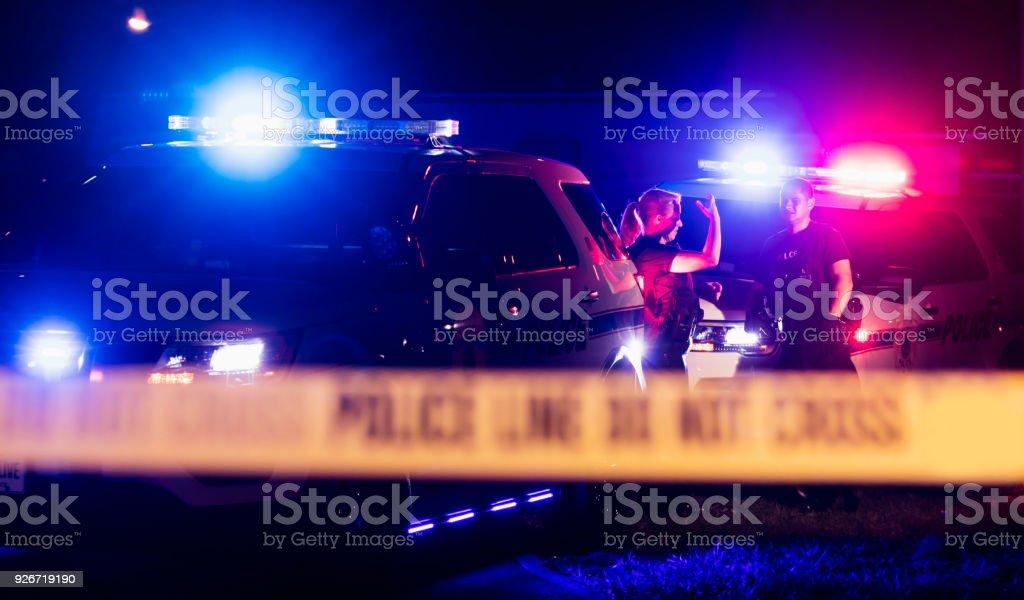 Police officers in bulletproof vests behind cordon tape stock photo