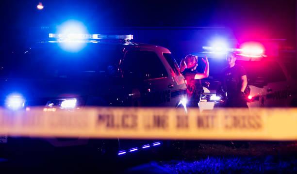 polizisten in kugelsichere westen hinter cordon band - tatort von menschen geschaffener raum stock-fotos und bilder