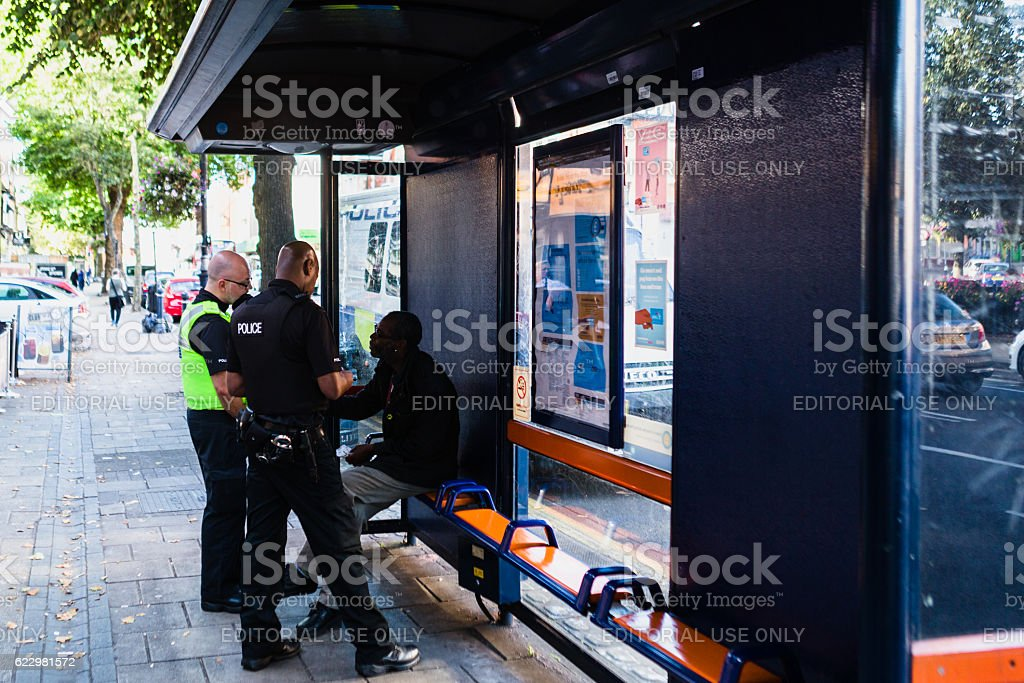 Police officers interviewing a man at a bus shelter stock photo