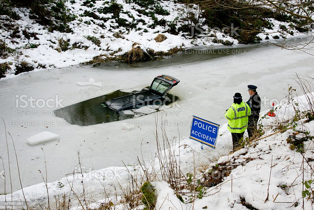 Police Officers observe car in frozen canal stock photo