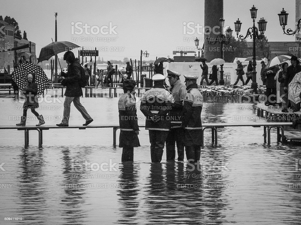 Police officers patrol in a flooded St Mark's Square stock photo
