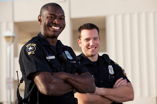 Multi-ethnic police officers (20s).  Focus on African American man.