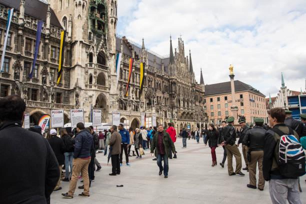 polizisten sehen in der nähe von einem infostand - arbeit in münchen stock-fotos und bilder