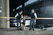 police officers with german shepherd on leash near cross line at crime scene