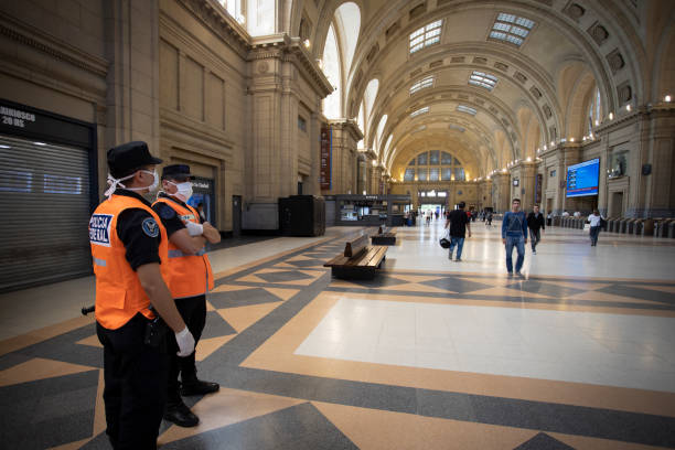 Polizisten mit Maske, die den Bahnhof kontrollieren – Foto