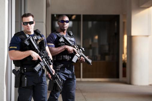 Multi-ethnic police officers (20s) wearing bulletproof vests, holding rifles.  Main focus on African American man.