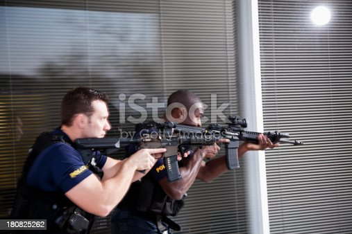 Multi-ethnic police officers (20s) with rifles.