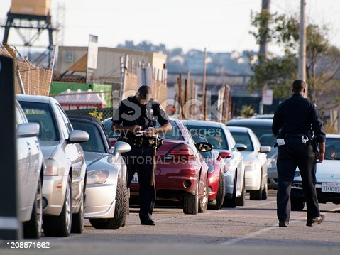 San Francisco  - October 9, 2011:  SFPD Police officers write parking tickets for cars along street during the day.