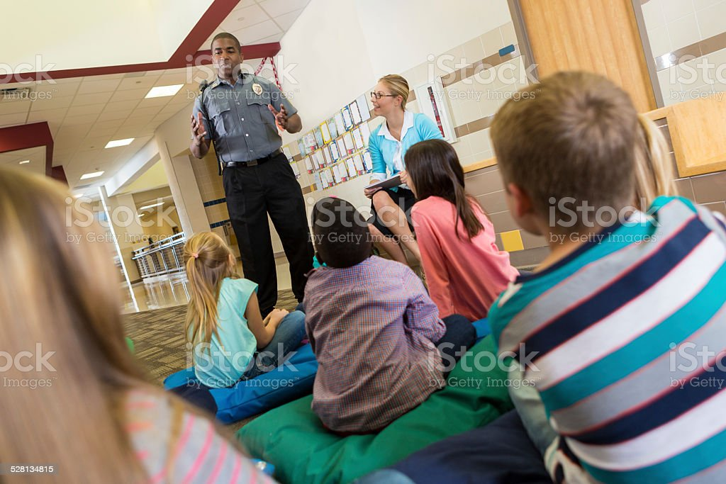 Police or school security officer speaking to young students Police or school security officer speaking to young students. Adult Stock Photo