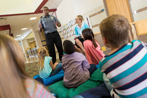Police Or School Security Officer Speaking To Young Students Stock Photo - Download Image Now