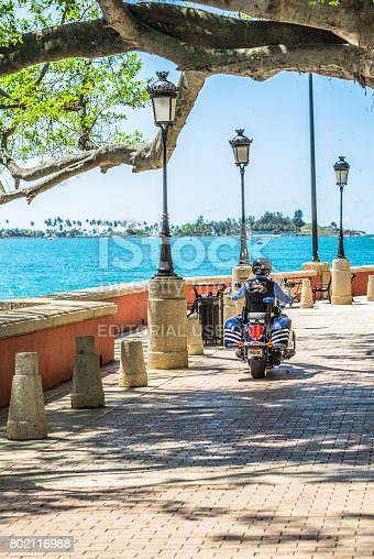 San Juan, USA - March 29, 2017: A police officer patrolling at Paseo de la Princesa. Constructed in 1853, Paseo de la Princesa is known as one of the world famous scenic walkways. It starts from a tree lined pedestrian stree of Old San Juan, leads towards Raices Fountain, Gate of Old San jUan, and ends at Castillo San Felipe Del Morro.