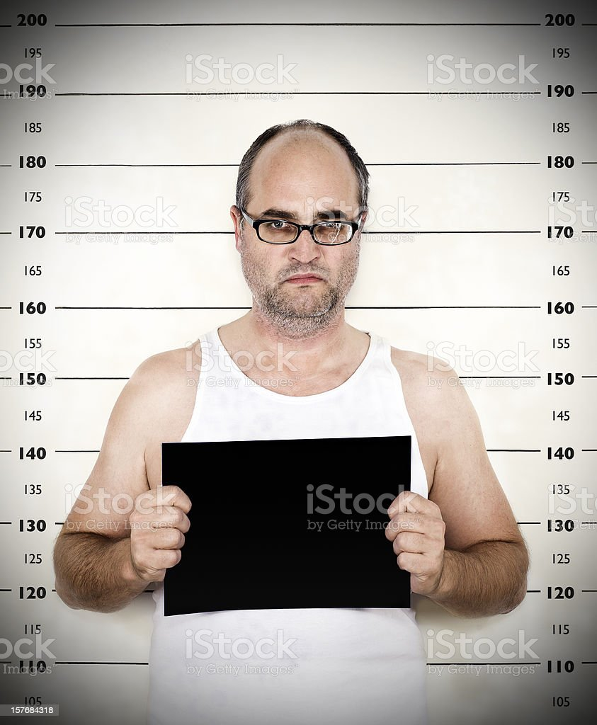 Police photo of arrested man with measuring scale in back stock photo