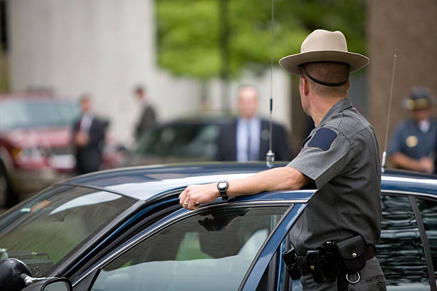 """Police """"A state trooper surveys a security detail while detectives, federal agents, and secret service mill about in the background"""" trooper stock pictures, royalty-free photos & images"""