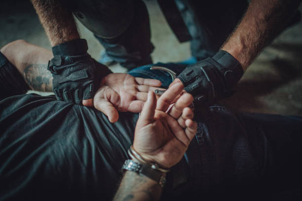 Police putting handcuffs on a man Special police forces man, making an arrest, putting handcuffs on a man/ counter terrorism stock pictures, royalty-free photos & images