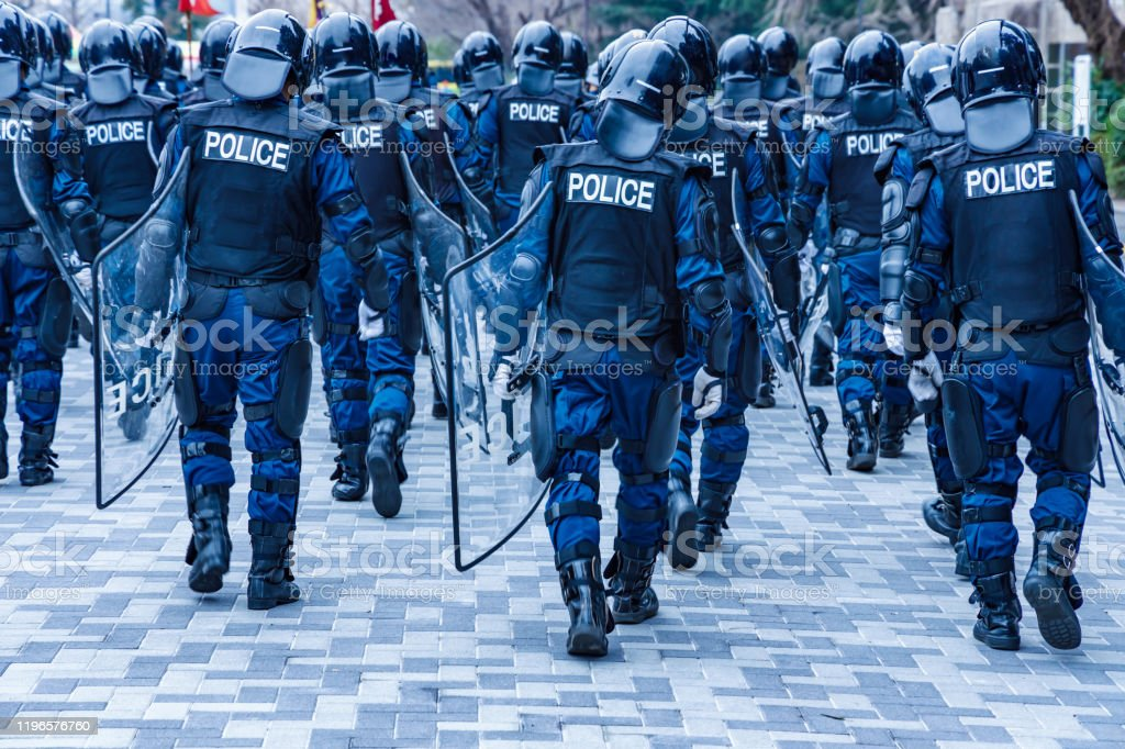 Police riot police protecting the peace of the city Police riot police protecting the peace of the city Adult Stock Photo