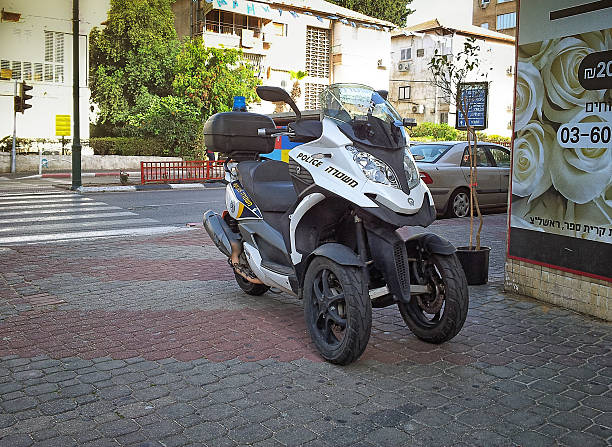 Police scooter Quadro 350 S3 in Israel Rishon Le Zion, Israel - April 7, 2015:  Police black-silver scooter Quadro 350 S3 staying on sidewalk Zhabotinsky Street. There are 3-story residential buildings in the background three wheel motorcycle stock pictures, royalty-free photos & images