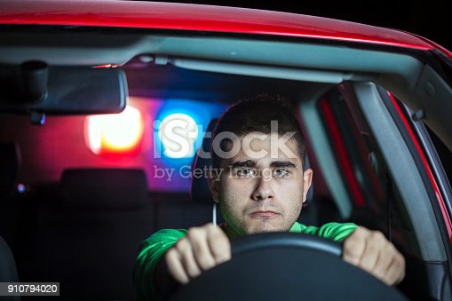 584585910istockphoto Police stopping a driver at night 910794020