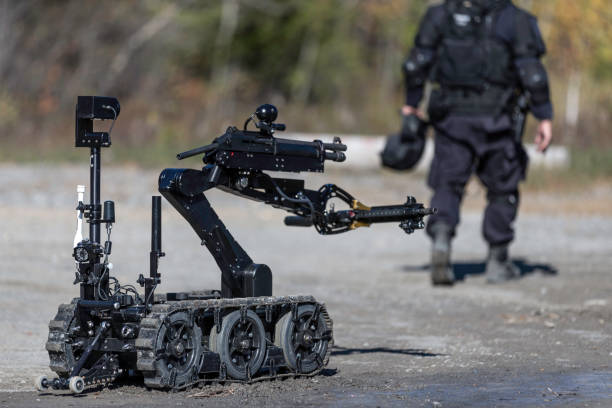 Police Swat Officer Using a Mechanical Arm Bomb Disposal Robot Unit Police Swat Officer Using a Mechanical Arm Bomb Disposal Robot Unit counter terrorism stock pictures, royalty-free photos & images