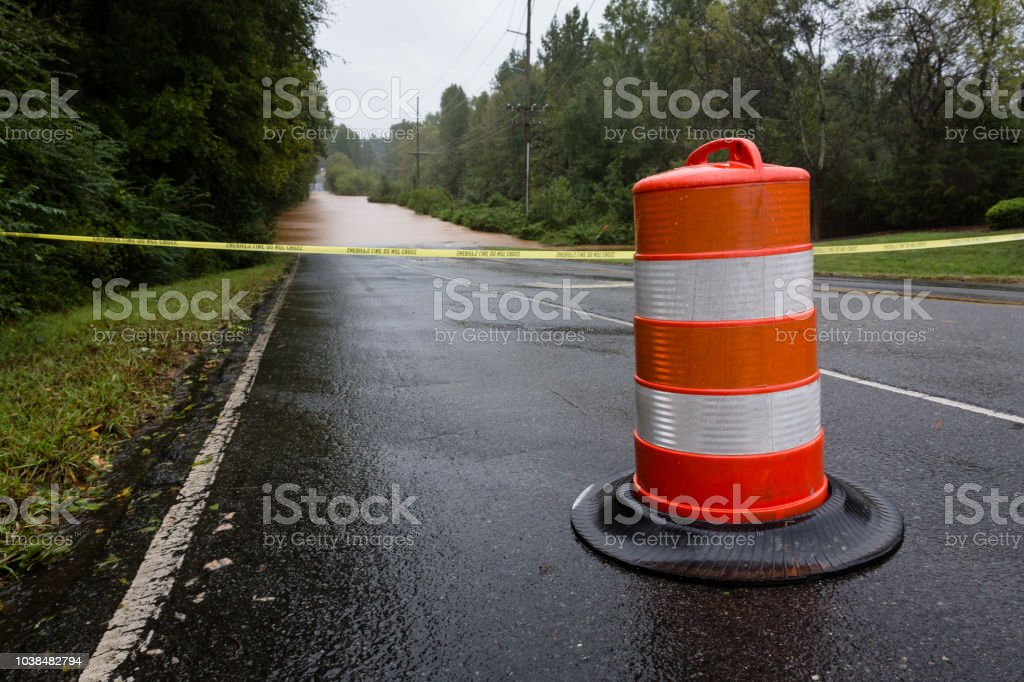 Police tape and a barricade block a flooded road stock photo