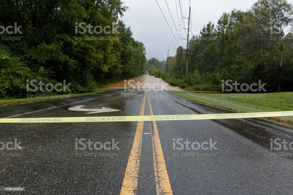 Police tape blocks a flooded road stock photo