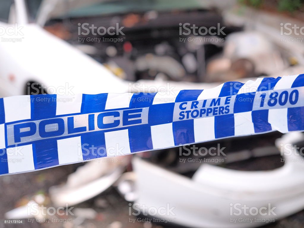 Police tape cordoning off a area with a damaged car stock photo