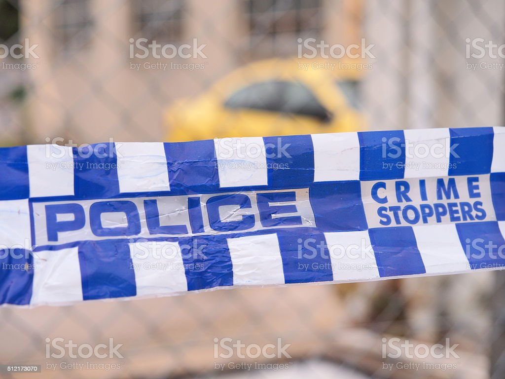 Police tape cordoning off a area with a yellow car stock photo