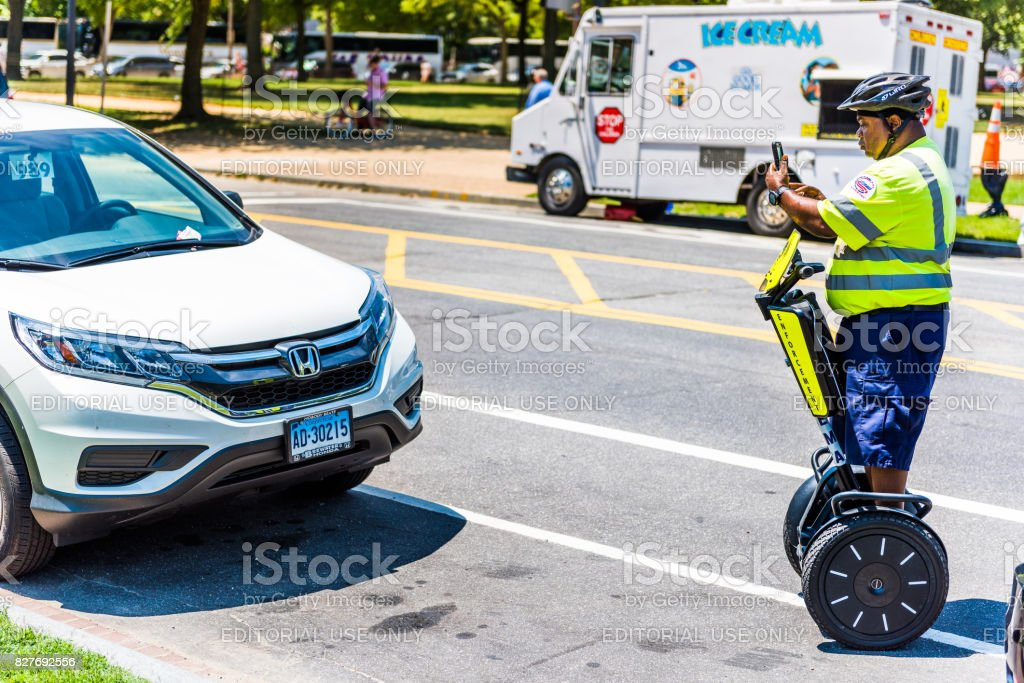 Police traffic officer writing ticket for car illegally parked while riding segway on national mall stock photo