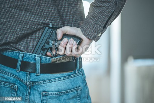 Undercover police agent is holding a black hidden weapon in his hand
