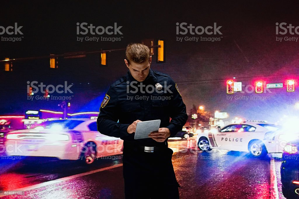 Police using tablet at night outdoors stock photo