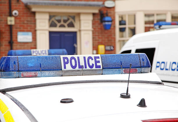 police vehicles parked outside a  station stock photo