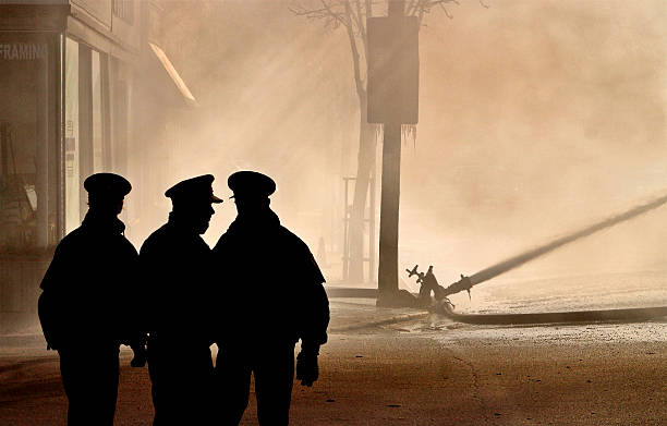 Police watching firefighters stock photo