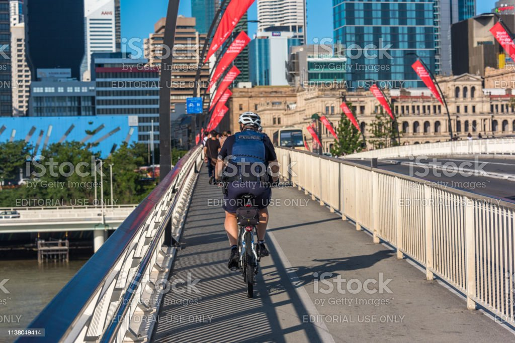Police worker cycling a bridge in Brisbane stock photo