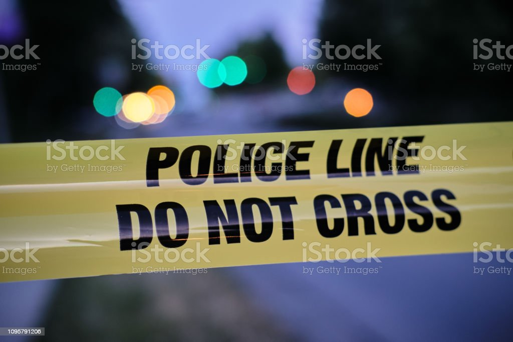 Police yellow line, blurred lights and traffic accident in background stock photo