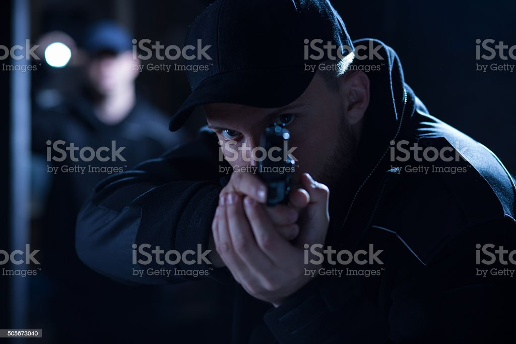Policeman aiming gun during intervention stock photo