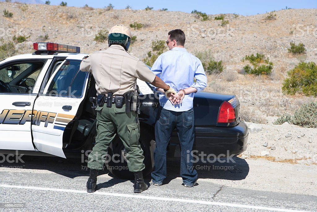 Policeman arresting criminal on road stock photo