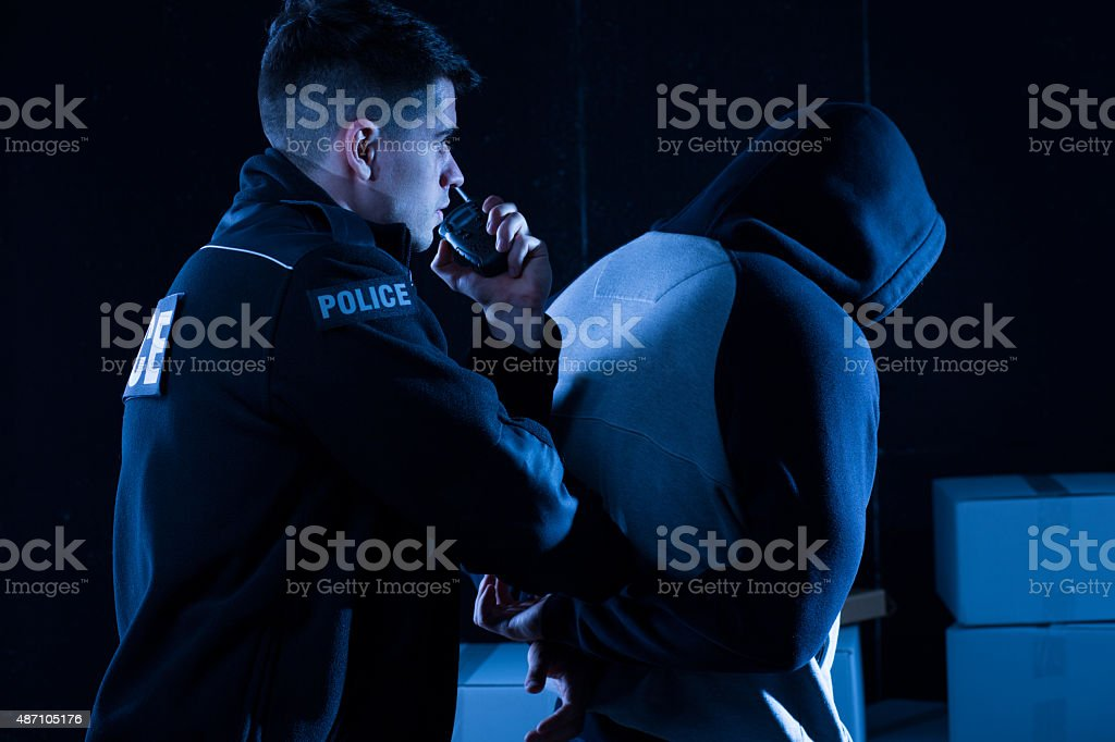 Policeman arresting law-breaker stock photo