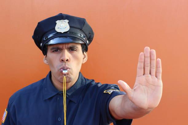 Polícia que funde o assobio e que mostra o gesto da mão do batente - foto de acervo