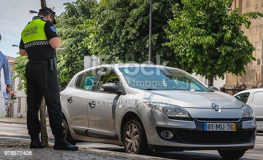istock policeman checks and writes a traffic ticket 976572408