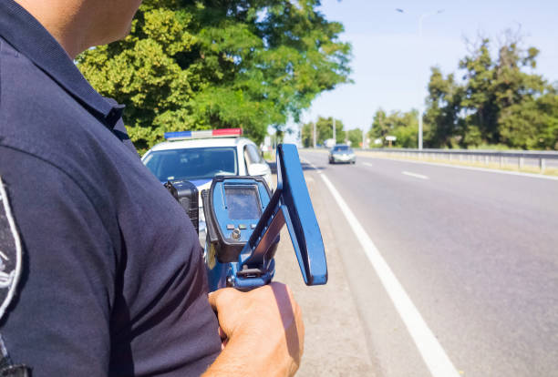 policeman holding laser speed gun near police car on highway background. selective focus, part of body. - radar foto e immagini stock