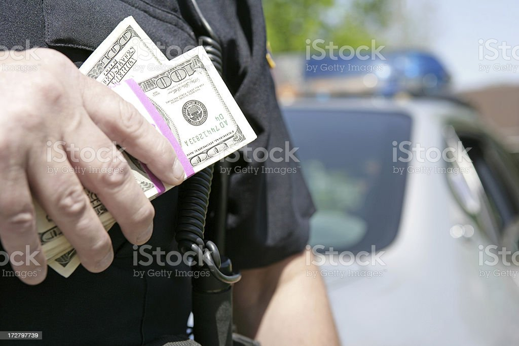 Policeman holding money stacks concept image for corruption stock photo